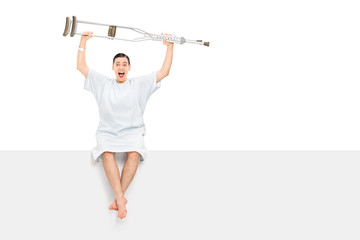 Overjoyed patient raising his crutches in the air