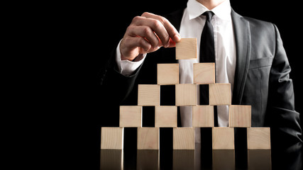 Businessman Arranging Wooden Blocks to Pyramid