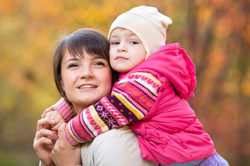 beautiful mother with toddler girl outdoors in fall