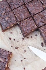 square of brownies cut with knife on baking paper