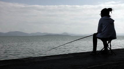 Little girl fishing in the lake - silouhette