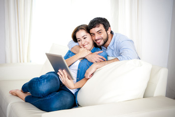 couple on couch enjoying using digital tablet computer