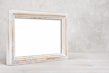 Old painted photo frame on table over abstract background