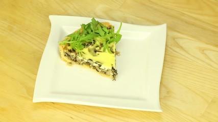 Piece of pie with mushrooms arugula
