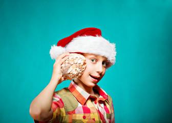 Funny child Santa holding a big sea shell smiling.