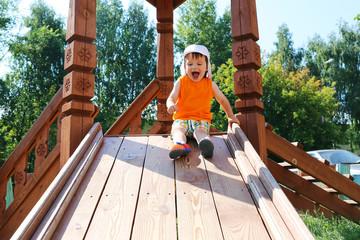 smiling toddler boy sliding on playground