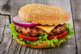 hamburger with grilled meat and cheese on a wooden surface