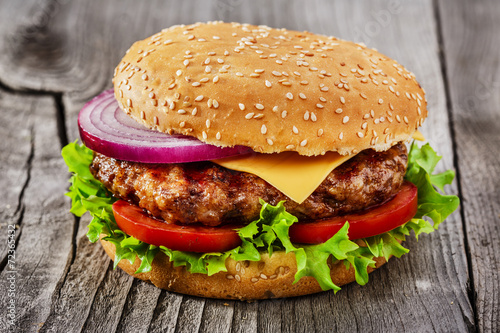 Poster Voorgerecht hamburger with grilled meat and cheese on a wooden surface