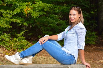 Beautiful young girl sitting on the bank in park