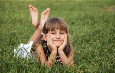 Cute little girl lies on a lawn in park and smiling