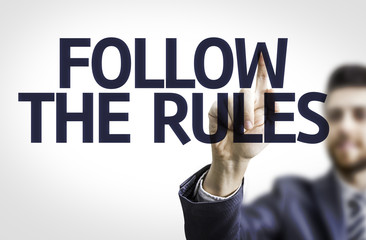 Business man pointing the text: Follow the Rules
