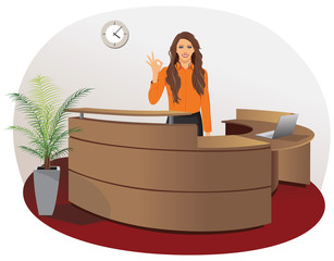 Smiling woman at office reception with okay gesture