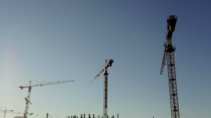 Time lapse silhouette crane working in construction site