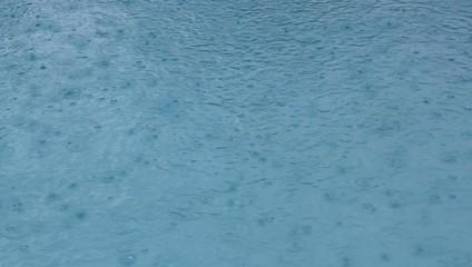 Regentropfen fallen in Swimmingpool