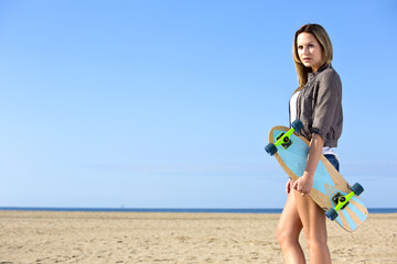 Woman walking on a beach with a skateboard