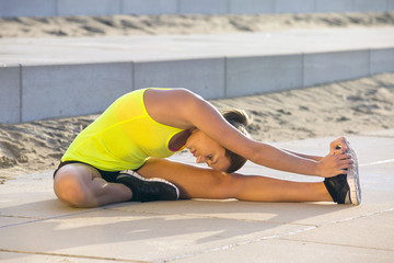 Flexible woman stretching on a beach boulevard