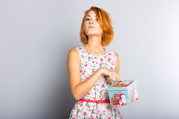 Beautiful red-haired girl with gift box in hands