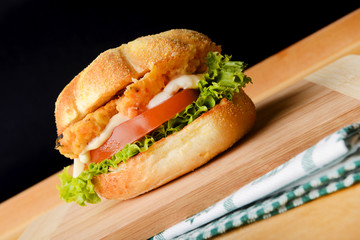 Appetizing fish burger on wooden board