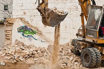 Abrissarbeiten - Ein Bagger auf einem Haufen Bauschutt