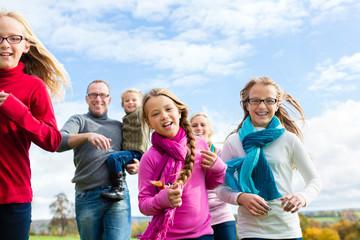 Familie läuft auf Wiese im Herbst Spaziergang