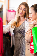 Frauen kaufen Kleidung im Laden ein
