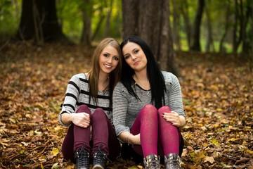 zwei Frauen sitzen im Herbst Wald