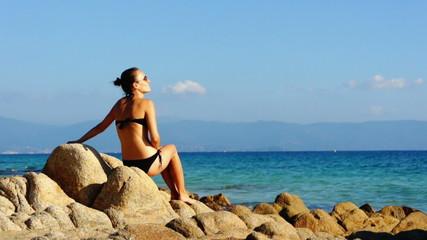 Woman in black bikini resting on the beach