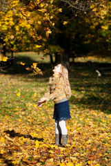 A pretty blond girl throwing up the tree leaves
