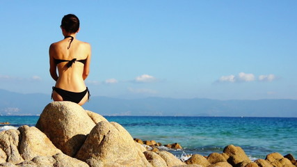 Young woman sitting by the blue mediterranean sea