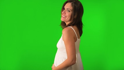 Beautiful pregnant woman holding her belly. Shot on Green Screen