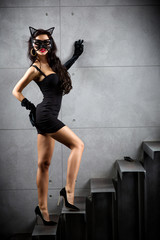 sexy woman in catwoman suit staying on stairs