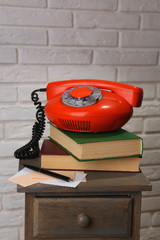 Retro phone on nightstand in room, close up