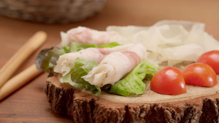 Tracking shot of lard roulades with salad and cherry tomatoes