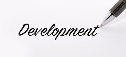 Pen write development word on paper.