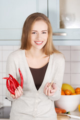 Caucasian woman holding chili peppers and garlic.