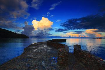 rock bridge into blue sea against beautiful morning light sky an