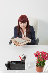 business woman reads book in a office