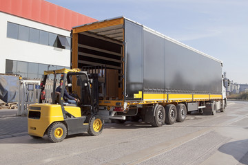 Logistics and Handling. Forklift is loading the truck.