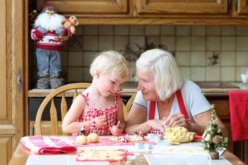 Grandmother making cookies together with granddaughter