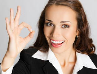 Businesswoman with okay gesture, over grey
