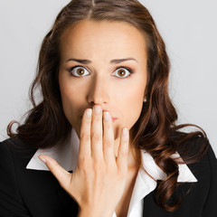 Business woman covering with hands her mouth, over grey