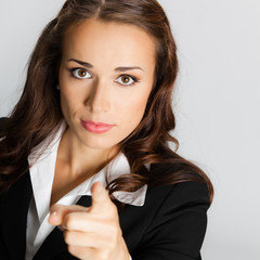 Serious business woman pointing finger at viewer, over grey