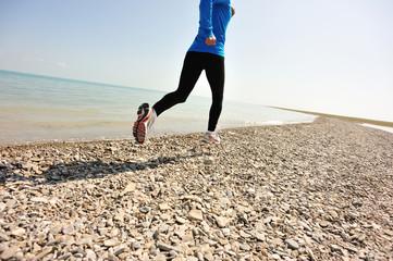 Runner athlete running on stone beach of qinghai lake