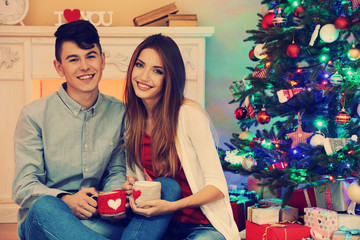 Nice love couple sitting with mugs in front of fireplace near