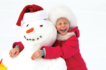 laughing little girl hugging a snowman