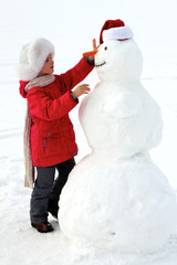 laughing girl sculpts big snowman