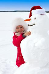 laughing little girl hugging a snowman