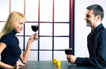 Young happy couple celebrating with red wine, indoors
