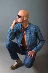 young bald man in jeans and glasses