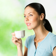 Young woman drinking coffee, outdoor